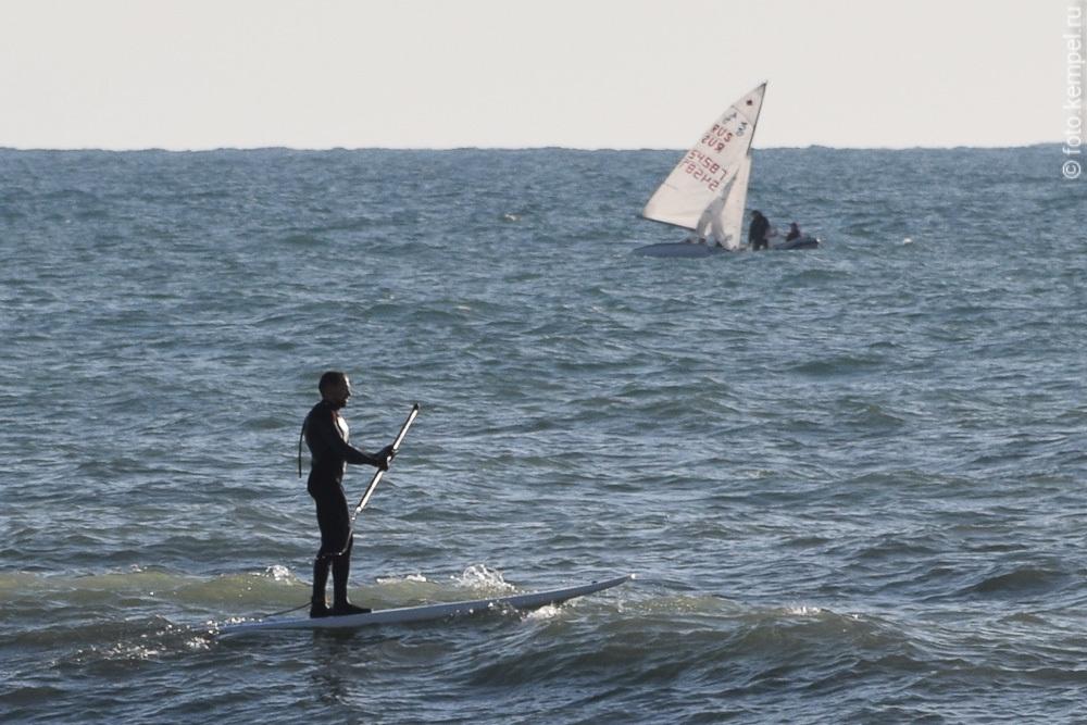Как выглядит море в Сочи в феврале. Яхта в Сочи в феврале, Серфингист в Феврале на сочинском пляже.